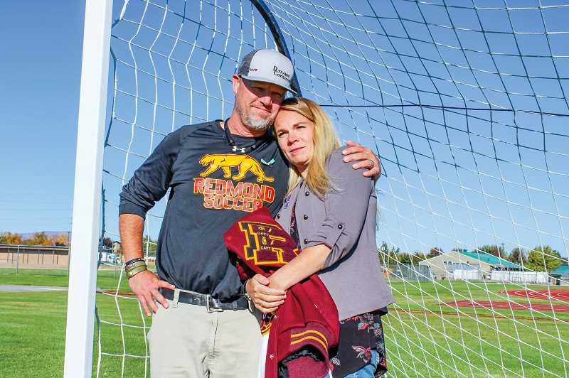 HOLLY SCHOLZ/CENTRAL OREGONIAN - Travis and Erika Holmes look out over the soccer field where their son, Hunter Holmes, once played as the Redmond High School goalkeeper. Hunter suffered two concussions during soccer games and took his life last December.