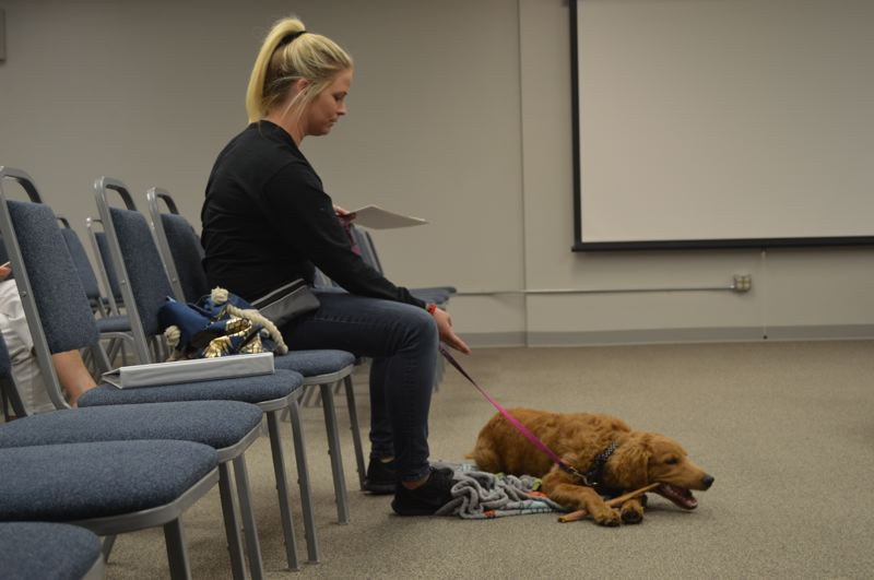 SPOTLIGHT PHOTO: NICOLE THILL-PACHECO - Whitney Scott, a Scappoose High School counselor, brings her dog Finley to a Scappoose School District board meeting on Monday, Sept. 24, to talk about how she plans to use the dog in the school as a therapy dog. Scott and Finley are currently going through a series of certified training classes to learn more about what it takes to be a therapy animal.