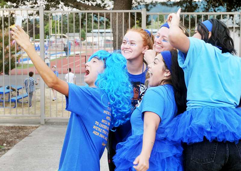 "SETH GORDON - Sophomore Asher Tatsumi takes a selfie with several classmates during the Tiger Tailgate event prior to Newberg High School's home football game Sept. 8. Many staff and students are reporting that the school is off to a great start this fall in part because of numerous efforts to create fun experiences for students. ""We're going to be here no matter what, so why not just make it good?"" Tatsumi said."