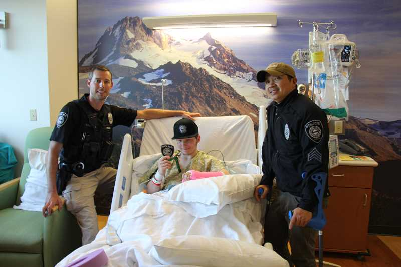 CONTRIBUTED PHOTO: GRESHAM POLICE DEPARTMENT - Gresham Polices Ben Costigan and Hung Nguyen visited a young fan, Christopher Bond, who was in the area for a surgery.
