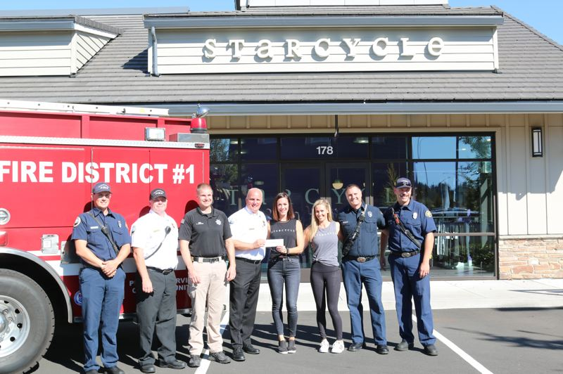 PHOTO COURTESY: TRACEY GRISHAM - From left to right: Clackamas Firefighter Dallas Oja; Battalion Chief John Hopkins; Happy Valley Police Department Chief Scott Anderson; Fire Chief Fred Charlton; Kelly Mreen and Heather Hedges, co-owners of StarCycle; Lieutenant David Aasland; and Apparatus Operator Alan Pernich.