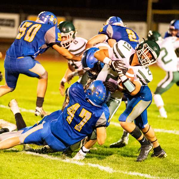 LON AUSTIN/CENTRAL OREGONIAN - Clayton Berman, 47, leads a group of Crook County defensive players as they tackle North Marion's Samuel Garcia for a short gain.