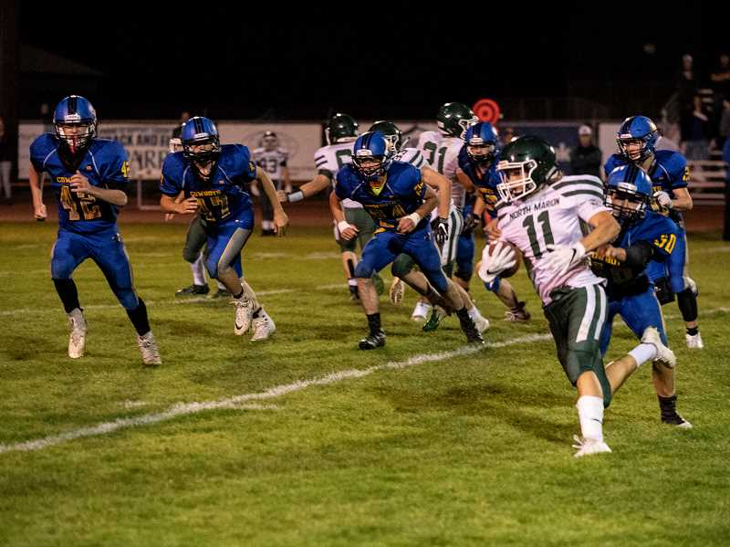LON AUSTIN/CENTRAL OREGONIAN - Crook County defenders pursue North Marion's Joe Torian, eventually tackling him for a short gain.