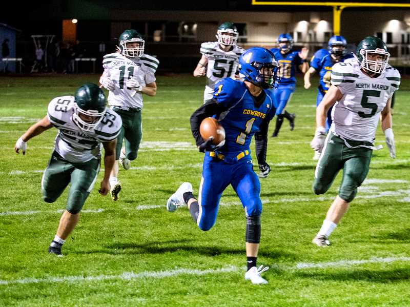 LON AUSTIN/CENTRAL OREGONIAN - Crook County's Dominic Langley races past North Marion's Joe Ledesma. 53. amd David Page, 5, on his way to the end zone. Langley's 82-yard touchdown dash helped give the Cowboys a 37-12 victory over the Huskies.