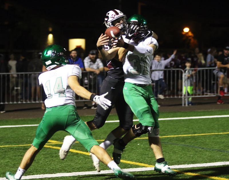 TIMES PHOTO: DAN BROOD - West Linn senior Tanner Moore (14), Sherwood senior Michael Klapp and West Linn senior Max Jacobs battle for the ball during Friday's game. Jacobs came away with an interception on the play.