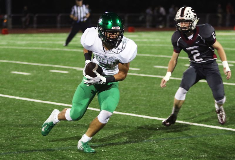 TIMES PHOTO: DAN BROOD - West Linn senior receiver Cade Knutson (left) looks for yardage after catching a pass during Friday's game at Sherwood.
