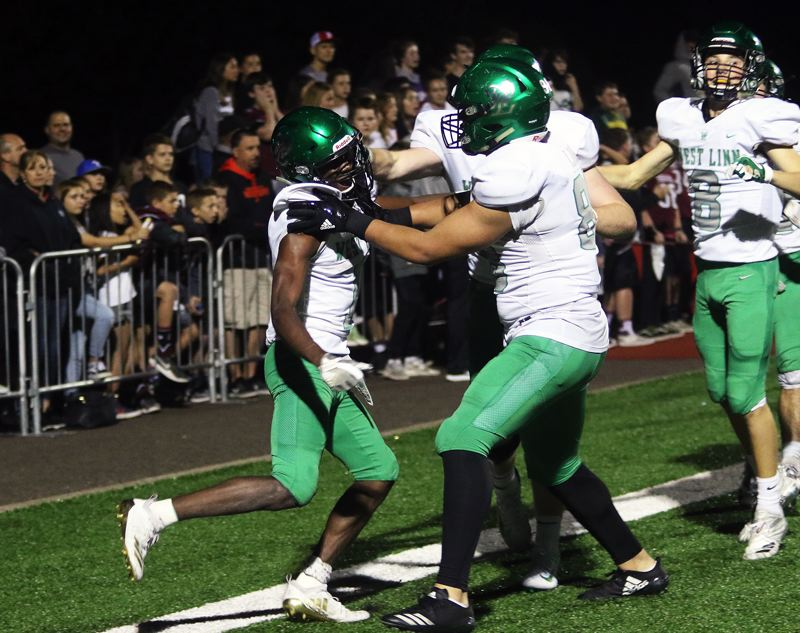 TIMES PHOTO: DAN BROOD - Members of the West Linn football team celebrate with senior Dawson Jolley (left) following his game-winning touchdown in double overtime during Friday's game at Sherwood.