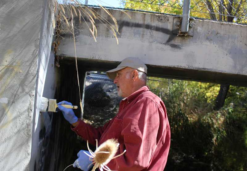 JASON CHANEY - Prineville resident Lynn Troupe paints over the top of graffiti on a bridge footing west of Main Street along Ochoco Creek. More of the graffiti is shown below.