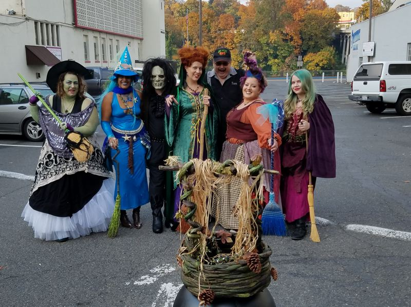 SUBMITTED PHOTO - Ghoul Gallery owner Tom Geil is surrounded by the PDX Dancing Witches group in downtown Oregon City.
