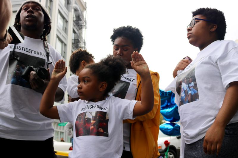 TRIBUNE PHOTO: ZANE SPARLING - A young girl raises her hands during a 'Hands up! Don't shoot!' chant on Monday, Oct. 1 during a downtown Portland vigil for Patrick Kimmons.