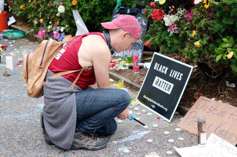 TRIBUNE PHOTO: ZANE SPARLING - A protester lights a candle near a 'Black Lives Matter' sign during a vigil for Patrick Kimmons, who was killed by Portland Police officers.