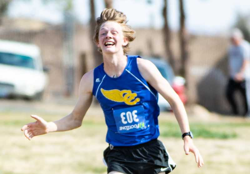 LON AUSTIN/CENTRAL OREGONIAN - Miles Chaney celebrates as he nears the finish line of the Madras Invitational. Chaney won the race, which was held at Kah-Nee-Ta on Saturday.