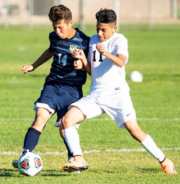 LON AUSTIN/CENTRAL OREGONIAN - Crook County's Kevin Arroyo and Pendleton's Miguel Rodriguez fight for the ball during the Cowboys' 2-1 victory over the Buckaroos. Arroyo scored both goals in the Cowboys' victory.