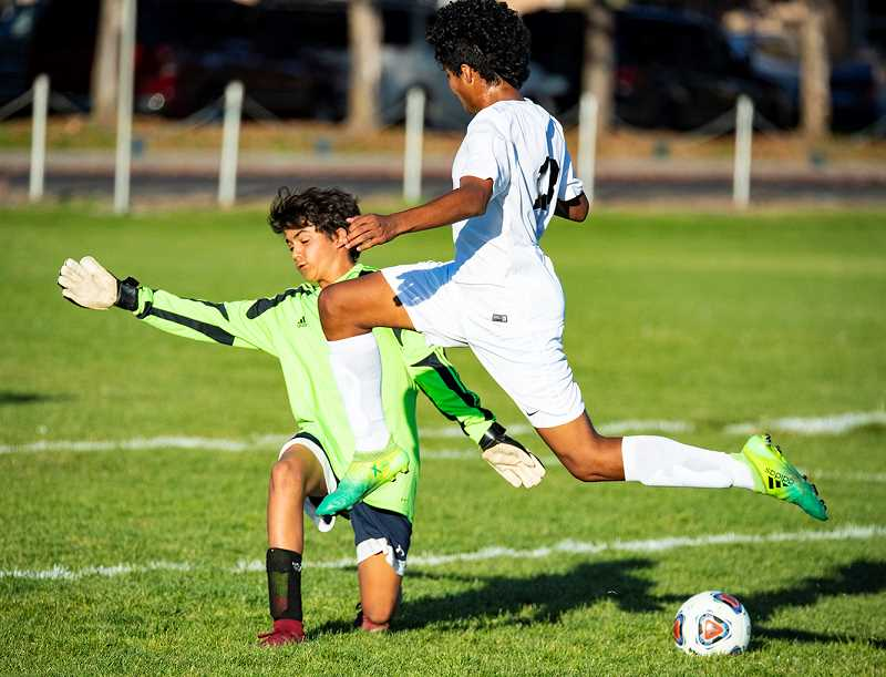 LON AUSTIN/CENTRAL OREGONIAN - Crook County goalkeeper Pablo Casado, in green, comes out of the goal to stop a shot during the Cowboys' 2-1 victory over the Pendleton Buckaroos last Thursday.