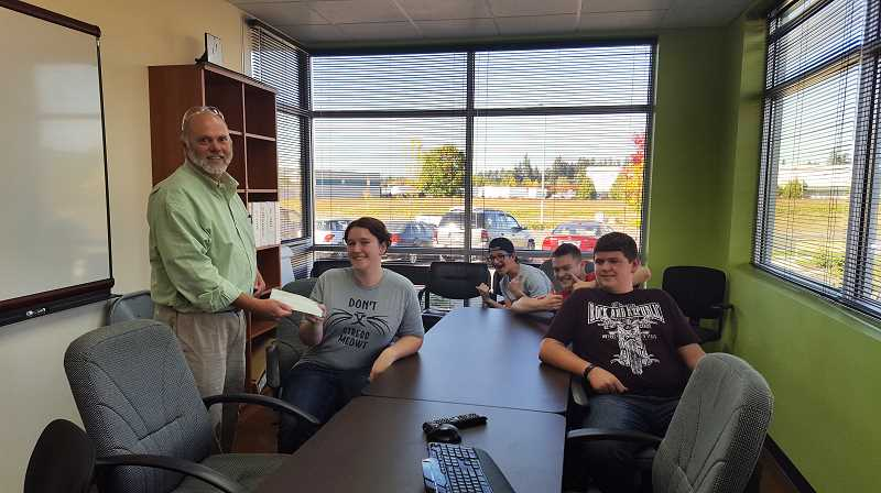 WENDY HUTCHINSON - Canby Robotics members receive a check from Cascade Engineering Technologies, Inc. President Dirk Ellis (left). The students are from left to right: Kaye Hutchinson, Alex Sunderland, Cole Kuehl and Ethan Porter.