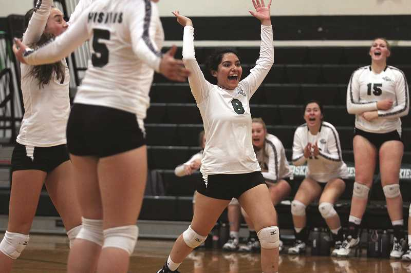 PHIL HAWKINS - North Marion senior Madeline Amezcua and the rest of the Huskies raise their hands in triumph after scoring the game-winning point against the Estacada Rangers on Sept. 25.