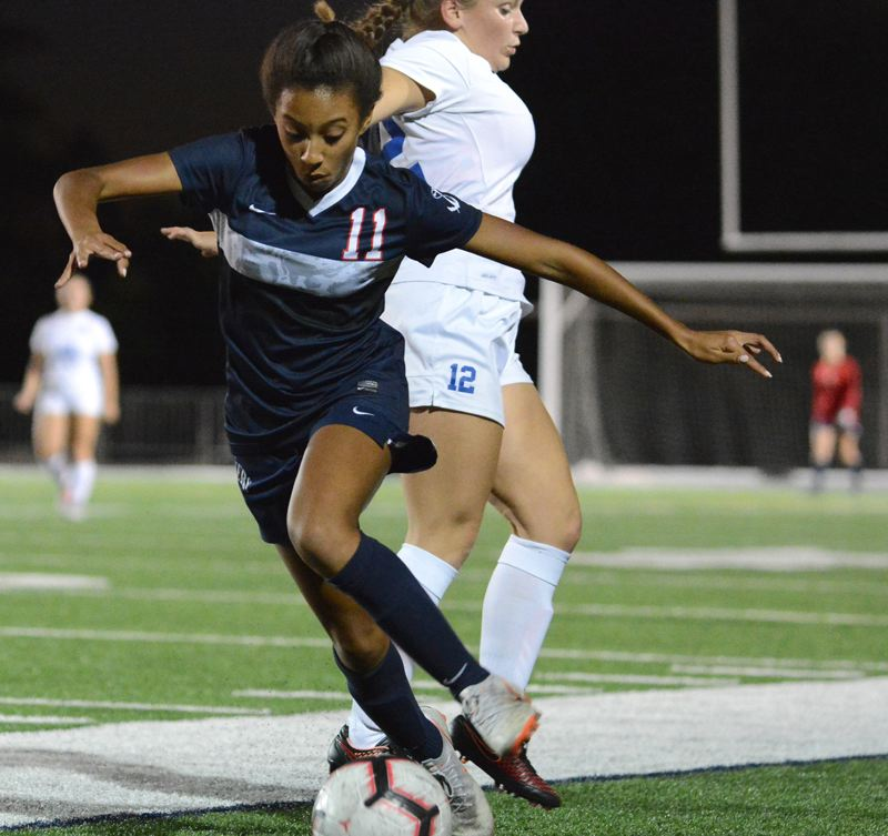 PAMPLIN MEDIA GROUP PHOTO: DAVID BALL - Lake Oswego's Jayden Hill moves along the sideline after getting around La Salle's Morgan Nebels during the Lakers' 3-0 home win on Sept. 25.