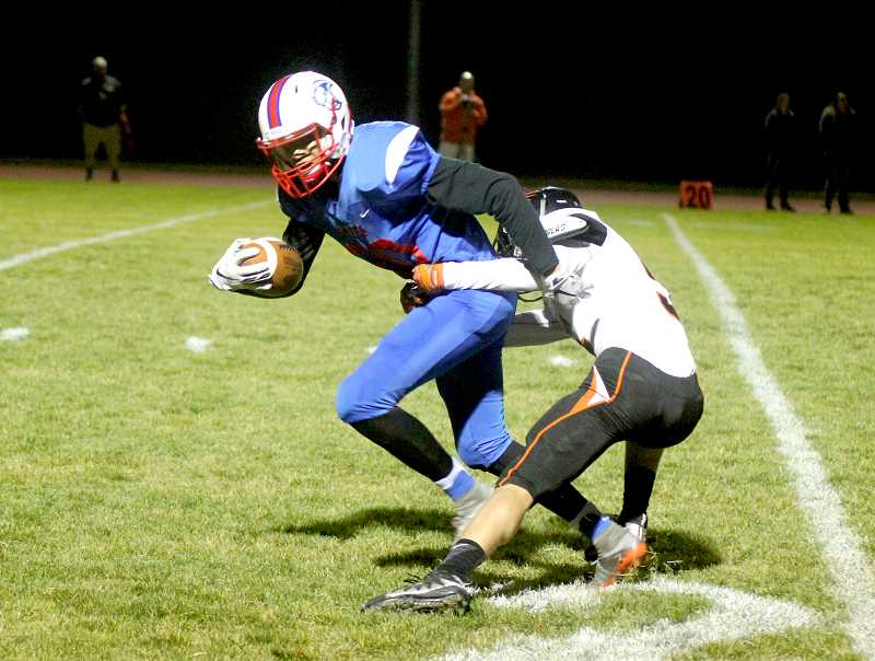 STEELE HAUGEN - Byron Patt tries to break through a Yamhill-Carlton defender. He finished the game with 95 yards receiving on five catches and two touchdowns.