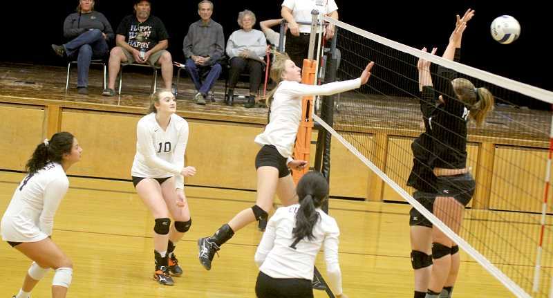 STEELE HAUGEN - Claire Bender spikes the ball past a pair of Western Christian blockers.