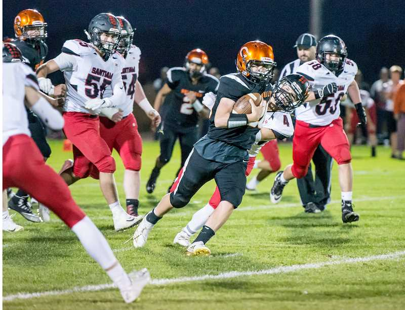 MARTY GOODSON FOR THE MADRAS PIONEER - Zach Wiseman runs the ball during the Dogs' 56-0 loss to Santiam.