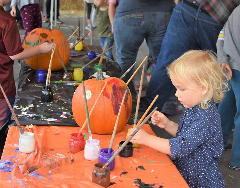 ESTACADA NEWS PHOTO: EMILY LINDSTRAND - A young attendee of the Estacada Harvest Festival decorates a pumpkin during the event on Saturday, Sept. 29.