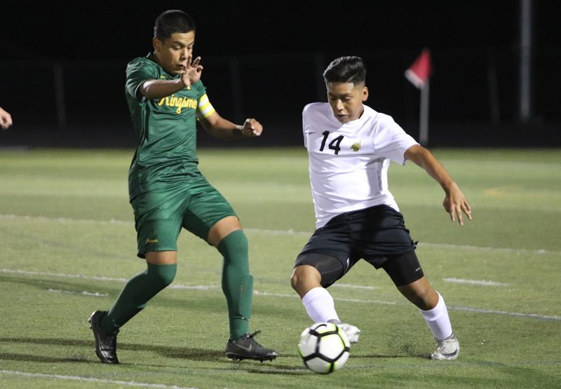 PAMPLIN MEDIA: JIM BESEDA - St. Helens' midfielder Jimmy Lopez (14) flicks the ball ahead under pressure from Putnam's Cesar Lopez-Hernandez during Tuesday's Northwest Oregon Conference boys' soccer match at Putnam.