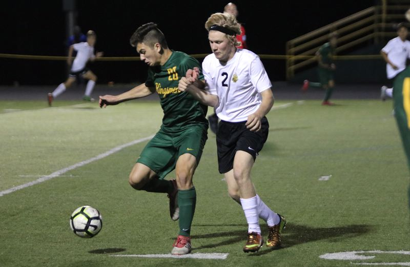 PAMPLIN MEDIA: JIM BESEDA - St. Helens defender Austin Hileman (2) challenges Putnam's Nicholas Reggiani for the ball during the second half of Tuesday's Northwest Oregon Conference boys' soccer match at Putnam High.