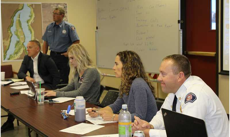 HOLLY GILL/MADRAS PIONEER - From right, Jefferson County Fire District Chief Brian Huff, moderator Katrina VanDis, administrative assistant LeeAnn Patton, Lt. Kirk Hagman, of JCFDD, standing, and Tim Gassner, attorney for the district, participate in the work session.