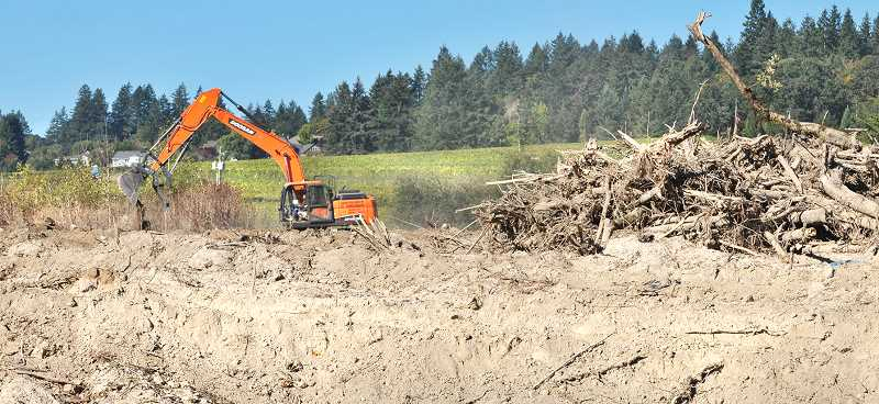 GARY ALLEN - An excavator works to cleaning up tons of cement and concrete from the land on Fox Farm Road in Dundee. The tentative plan is to develop a short term RV Park to house tourists visiting wine country.