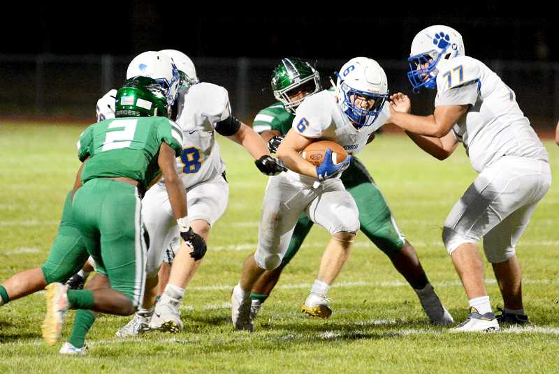 DAVID BALL -- GRESHAM OUTLOOK - Justin Holtan breaks through the line Friday night during Newberg's 28-14 road loss at Reynolds. Holtan carried the ball 12 times for 53 yards.