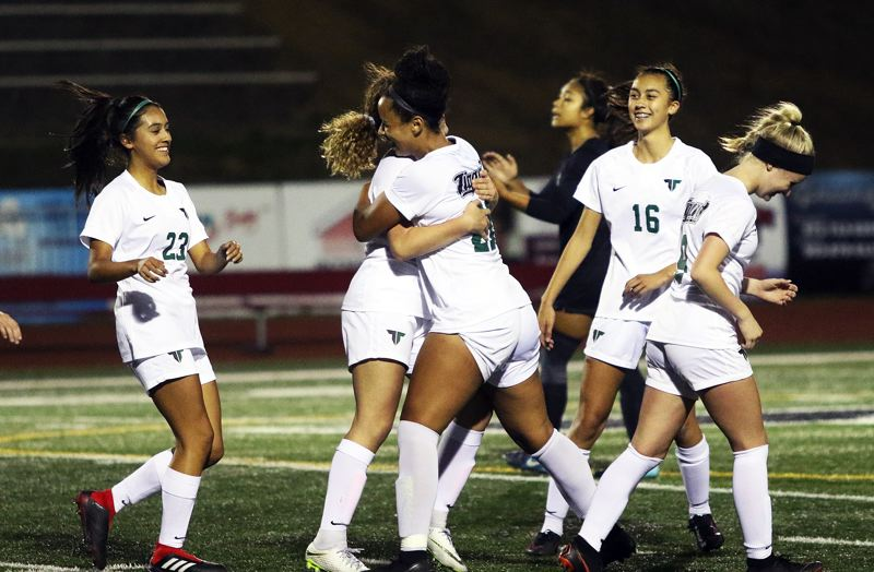 TIMES PHOTO: DAN BROOD - Tigard senior Gabby Brown (center) celebrates with her teammates, including junior Anette Hernandez (23) and Riley White (16) folling her second goal in the Tigers 2-1 win at Tualatin.