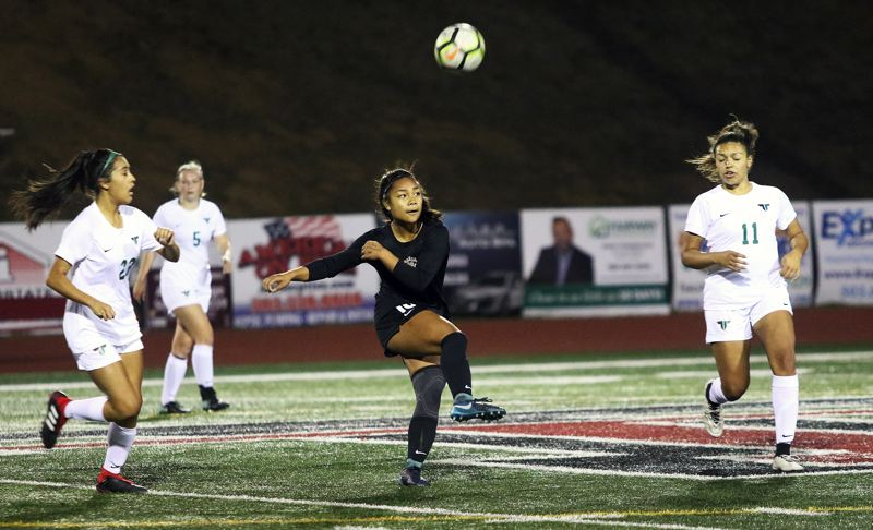 TIMES PHOTO: DAN BROOD - Tualatin High School sophomore Cally Togiai boots the ball during the Timberwolves Three Rivers League opener with Tigard on Tuesday.