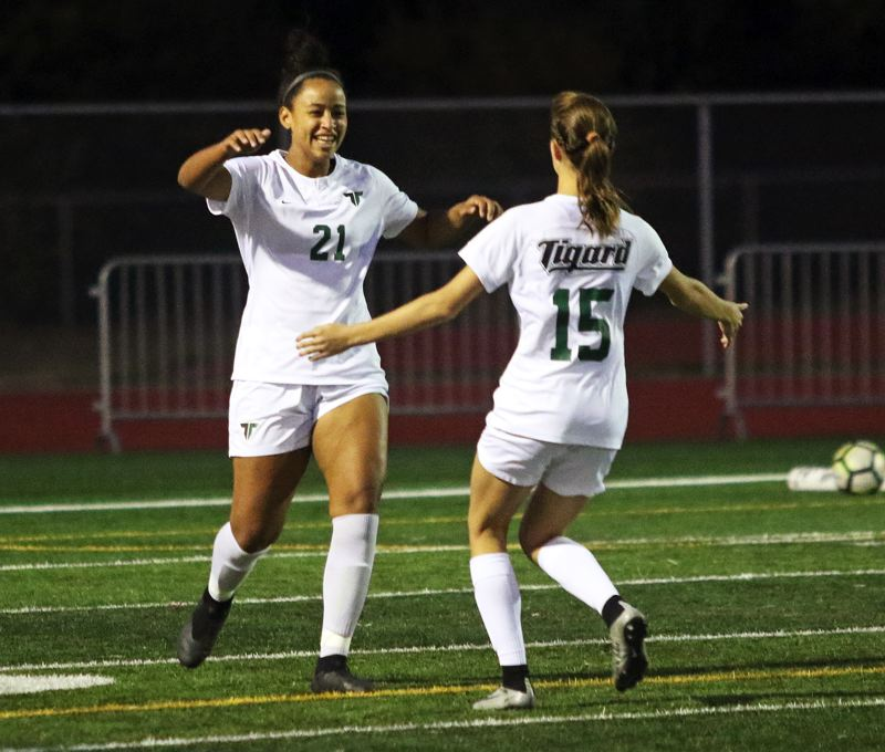 TIMES PHOTO: DAN BROOD - Tigard senior Gabby Brown (left) is going to get a hug from sophomore Lydia Emory after scoring the first of her two goals in the Tigers' 2-1 win at Tualatin.