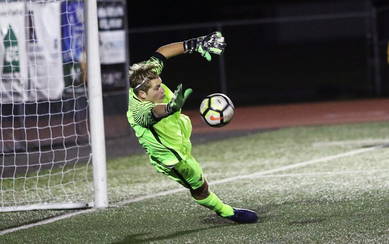 TIMES PHOTO: DAN BROOD - Tigard High School junior goalkeeper Jackson Cleaver makes a diving block of a Tualatin penalty kick during the Tigers 3-2 win on Tuesday