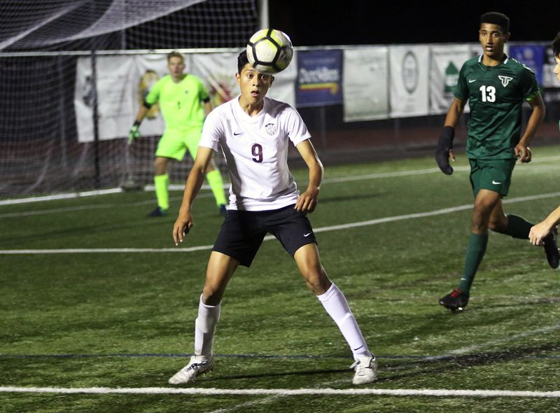TIMES PHOTO: DAN BROOD - Tualatin High School senior Mario Quiterio keeps his eyes on the ball during the Wolves match at Tigard on Tuesday.