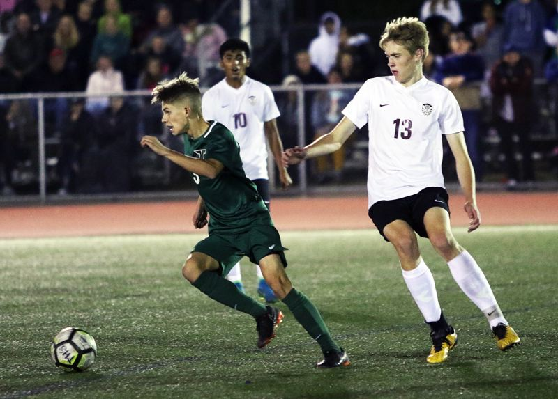TIMES PHOTO: DAN BROOD - Tigard junior Trevor Smith (left) takes off with the ball during the Tigers' 3-2 win over Tualatin on Tuesday.