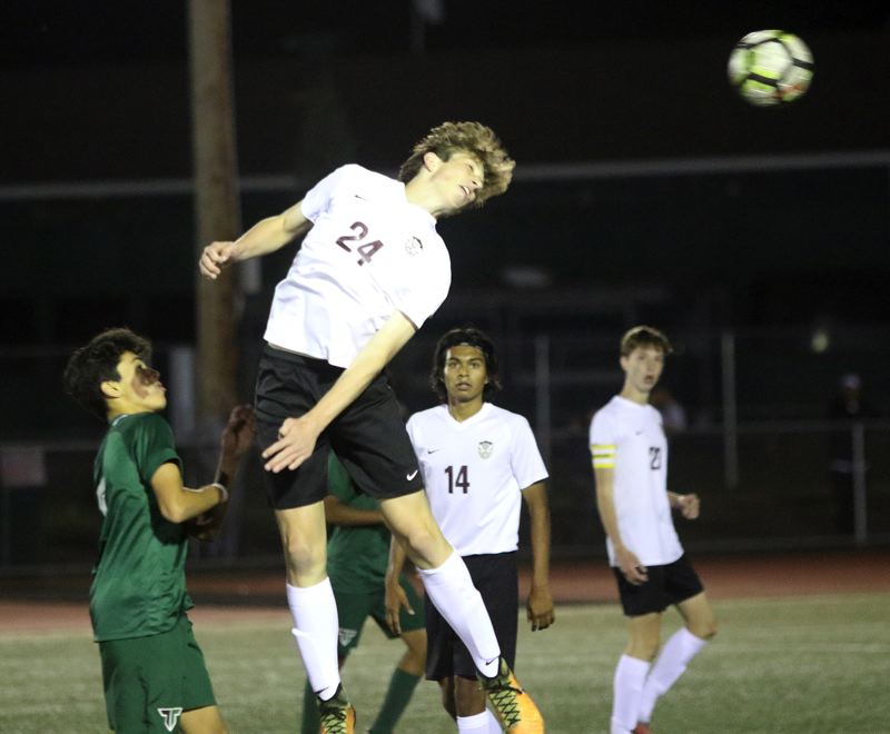 TIMES PHOTO: DAN BROOD - Tualatin junior Hunter Popma goes up high to head the ball during the Wolves' match at Tigard on Tuesday.