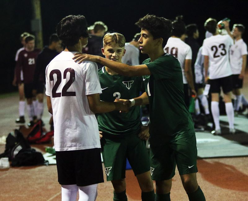 TIMES PHOTO: DAN BROOD - From left, Tualatin senior Christian Pumpelly, Tigard junior Trevor Smith and Tigard junior Rasheed Tarhuni talk after Tuesday's match.