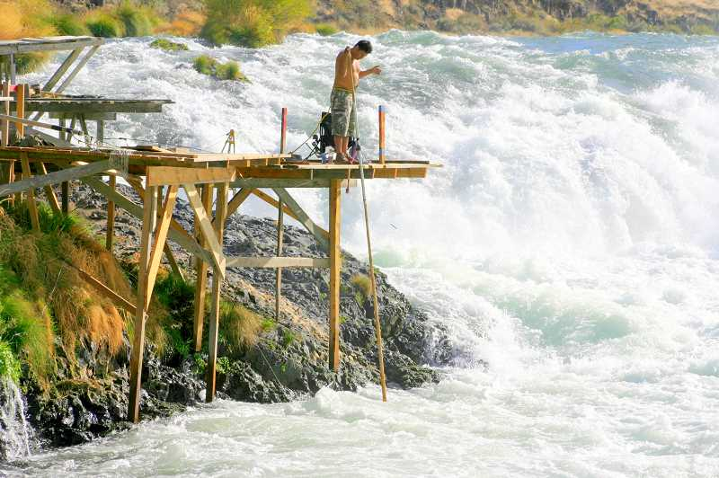 TIDINGS PHOTO: LESLIE PUGMIRE HOLE - With a safety tether on his waste, a fisher works on a platform at Sherar Falls on the Deschutes River.