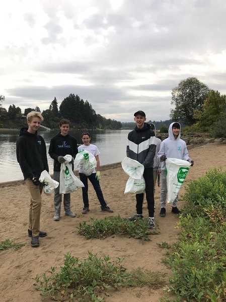 SUBMITTED PHOTO: TERRI JONES - NLYM members pick up trash off the banks of the Willamette River (from left): Jackson Davitt, Jackson Coder, Brooks Dennett, Sean Davitt, Sean Leiband and Marcus Whelan in the back.