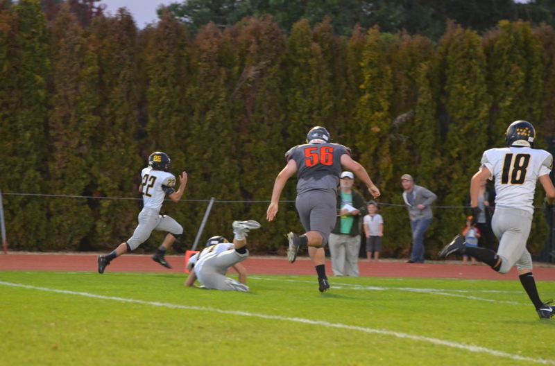 PHOTO COURTESY: JOHN BREWINGTON - Isaiah Bettencourt, a senior safety for the St. Helens Lions, returns an interception for a touchdown on the first play from scrimmage in the Sept. 28 game at Scappoose High.