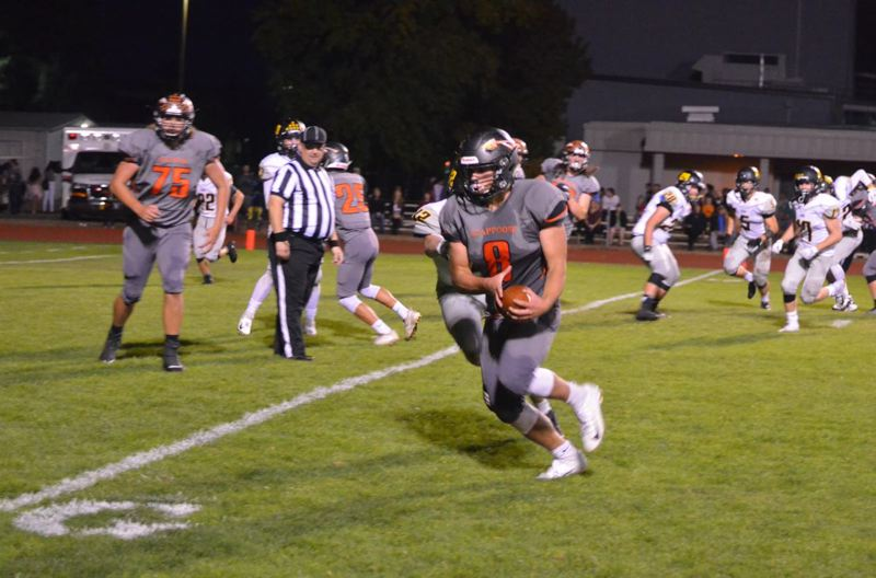 PHOTO COURTESY: JOHN BREWINGTON - Quarterback Jakobi Kessi gets outside to score an early touchdown for the Scappoose Indians as they defeat the St. Helens Lions, 49-25, on Sept. 28 at Scappoose High.