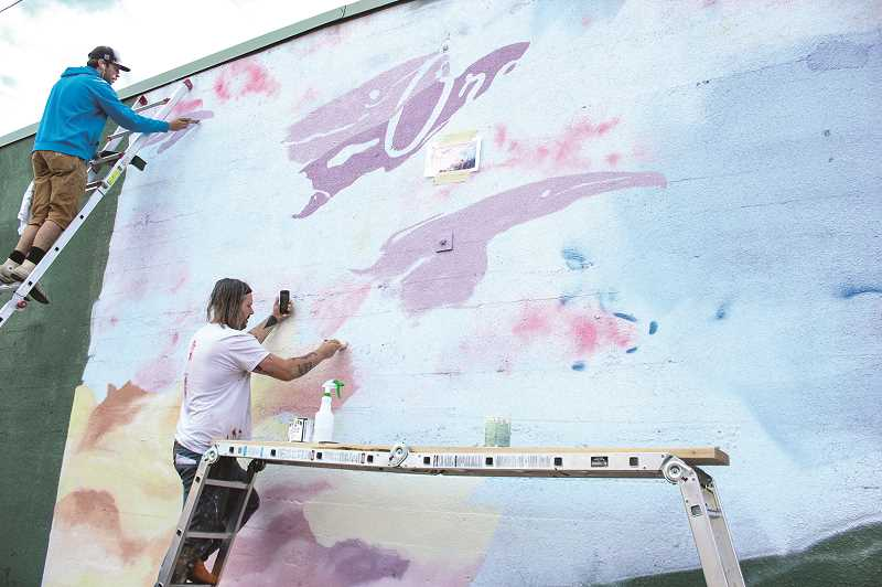 JASON CHANEY - Portland-based mural artists Zach Yarrington (left) and Gage Hamilton paint a mural on the north-facing wall of Crooked River Brewing on Wednesday afternoon. The project was expected to be done on Friday.