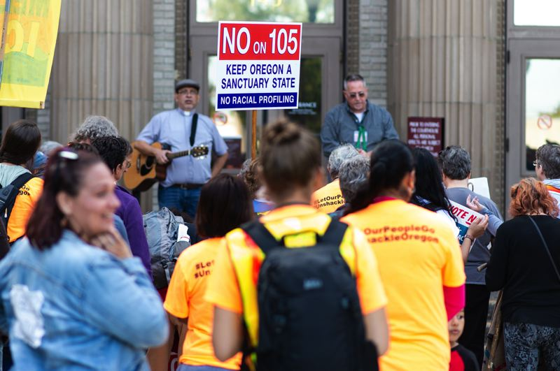 STAFF PHOTO: CHRISTOPHER OERTELL - A few dozen people congregated outside of the Washington County Courthouse singing songs and  chanting in protest of ICE and to encourage 'no' on Measure 105.