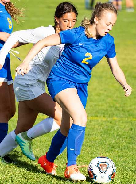 LON AUSTIN/CENTRAL OREGONIAN - Teagan Freeman plays the ball away from a Ridgeview defender Tuesday afternoon during the Cowgirls' 8-0 loss to the Ravens.