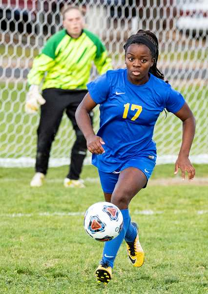 LON AUSTIN/CENTRAL OREGONIAN -  Zoe Guthrie pushes the ball up the field from near the Crook County goal in the match. Crook County goalkeeper Hazel Hoffman is in the background.