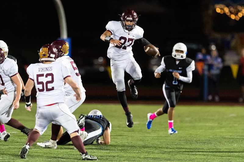 STAFF PHOTO: CHRISTOPHER OERTELL - Forest Grove's Dominic Funk leaps over a Hillsboro defender during the Vikings' game against the Spartans, Oct. 5, at Hare Field in Hillsboro.