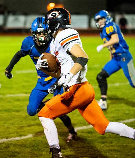 LON AUSTIN/CENTRAL OREGONIAN - Spencer Boyd carries the ball around left end for the Gladiators during their victory over Crook County Friday night.