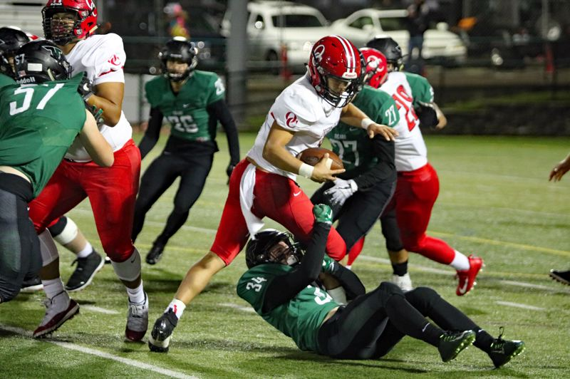 PAMPLIN MEDIA: JIM BESEDA - Tigard linebacker Cole Scott (34) brings down Oregon City quarterback Colby Iverson for a 1-yard loss during the third quarter of Friday's 6A Special District 5 football game at Tigard High School.