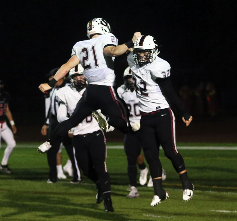 TIMES PHOTO: DAN BROOD - Sherwood seniors Kaden Rhinehart (21) and Ian Stormont celebrate following a Stormont touchdown run during the Bowmen's 38-27 win at McMinnville.